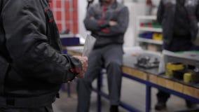 O mestre está dando para papéis do trabalhador com especificação técnica em uma oficina da produção da fábrica durante o encontro filme