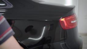 O mestre está lustrando uma parte traseira do automóvel pelo pano macio vermelho na auto oficina após o lavagem filme