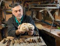 O mestre examina os carvings de madeira, das verificações do carpinteiro terminado Imagem de Stock
