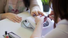 O mestre faz o tratamento de mãos do hardware O manicuro está aplicando a broca elétrica do arquivo de prego ao tratamento de mão video estoque