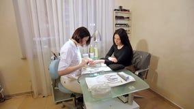 O mestre faz os pregos lisos usando o arquivo de prego Conceito do processo do tratamento de m?os vídeos de arquivo