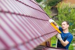O mestre no reparo dos telhados faz a ferramenta das medidas imagem de stock