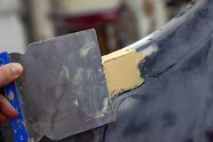 O mestre no trabalho em uma oficina do carro aplica uma massa de vidraceiro com um revestimento para rebocar um amortecedor de re fotografia de stock