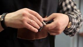 O mestre põe uma curvatura sobre a correia de couro Procedimento para fabricar a correia de couro video estoque