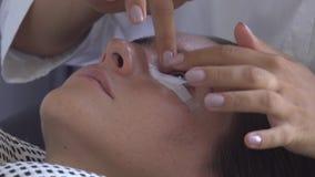 O mestre profissional do chicote pôs a proteção sobre o olho dos modelos Extensão da pestana no estúdio da beleza filme