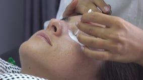 O mestre profissional remove o óleo com o botão do algodão do olho dos modelos Preparação antes da extensão da pestana no estúdio filme