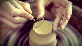 O mestre remove a camada superior de argila em um potenciômetro de argila com uma ferramenta especial filme