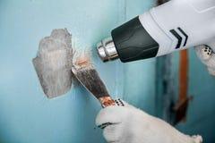O mestre remove a pintura velha da janela com a arma e o raspador de calor closeup fotos de stock royalty free