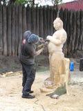 O mestre trabalha acima da criação da escultura de madeira Imagens de Stock