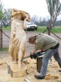 O mestre trabalha acima da criação da escultura de madeira Imagem de Stock