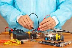 O mestre verifica a placa eletrônica com o multímetro na oficina do serviço Fotografia de Stock