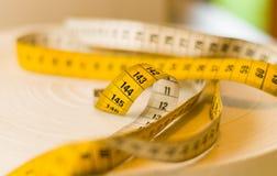 O mesure amarelo da fita rolou na parte superior de uma tabela, centímetros e mede o messurement Fotos de Stock