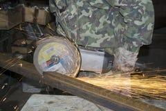O metal com uma serra, faíscas do sawing do trabalhador voa Imagens de Stock