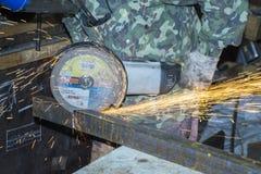 O metal com uma serra, faíscas do sawing do trabalhador voa Imagem de Stock