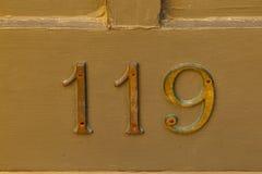 O metal muito velho numera no lado de uma construção Foto de Stock