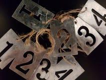 O metal numera etiquetas com uma corda Imagem de Stock Royalty Free