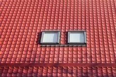 O metal vermelho telhou o telhado com trapeiras novos, o telhado Windows, as claraboias e a proteção do telhado da placa da neve Fotografia de Stock Royalty Free