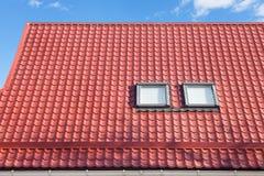 O metal vermelho telhou o telhado com trapeiras novos, o telhado Windows, as claraboias e a proteção do telhado da placa da neve Imagem de Stock