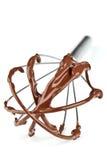 O metal whisk com chocolate fotografia de stock royalty free