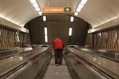 O metro de Budapest, um homem escala acima as escadas imagem de stock