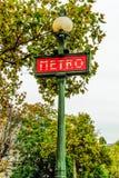 O metro do estilo antigo assina dentro Paris com arquitetura no fundo, França imagem de stock