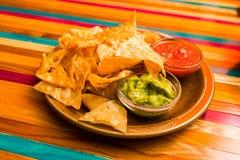 O mexicano lasca nachos em uma placa, fotos de stock royalty free