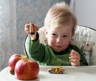 O miúdo agradável fair-haired com maçãs vermelhas Foto de Stock Royalty Free