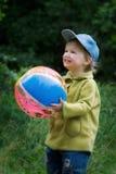 O miúdo alegre com uma esfera Imagens de Stock Royalty Free