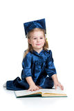 O miúdo da menina no academician veste o livro de leitura foto de stock