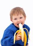 O miúdo de sorriso come a banana Fotos de Stock Royalty Free