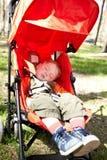 O miúdo dorme no buggy Imagem de Stock