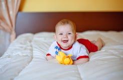 O miúdo feliz pequeno encontra-se em uma cama foto de stock royalty free