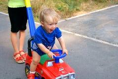 O miúdo pelo carro das crianças Foto de Stock Royalty Free