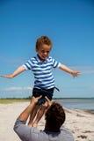 O miúdo que aprecia como seu paizinho levanta-o Imagens de Stock