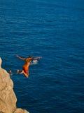 O miúdo que salta na água Fotos de Stock