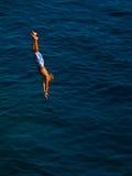 O miúdo que salta na água Fotos de Stock Royalty Free