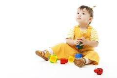 O miúdo senta-se e joga-se com brinquedo Foto de Stock Royalty Free
