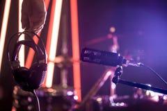 O microfone e os fones de ouvido do estúdio na mão de uma pessoa fecham u Foto de Stock
