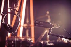O microfone e os fones de ouvido do estúdio na mão de uma pessoa fecham u Imagens de Stock