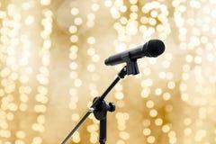 O microfone sobre o brilho romântico do fundo dourado do bokeh do amarelo do ouro do borrão ou luxuoso bonito ilumina a máscara p fotos de stock royalty free