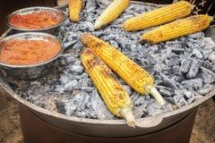 O milho de Fried Mexican com pimenta vermelha é girado em carvões quentes fotografia de stock