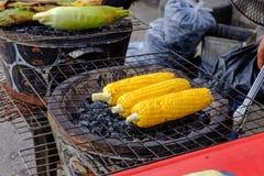 O milho doce é cozido com carvão vegetal que o alimento é processado a um novo Fotografia de Stock