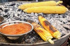 O milho no estilo mexicano com pimenta vermelha é cozinhado em carvões quentes fotografia de stock royalty free