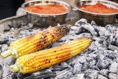O milho no estilo mexicano com pimenta vermelha é cozinhado em carvões quentes Fast food na rua fotos de stock royalty free