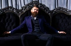 O milionário no terno elegante senta-se no sofá luxuoso fotos de stock royalty free