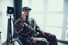 O militar deficiente fala o telefone na cadeira de rodas fotos de stock