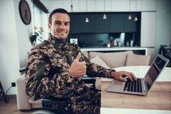 O militar na cadeira de rodas usa os polegares do portátil acima foto de stock royalty free