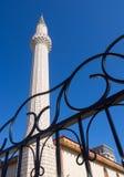 O minarete de mesquitas muçulmanas e um fragmento de cerca feita do metal fotografia de stock royalty free