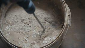 O misturador bonde mistura o cimento em uma cubeta em um canteiro de obras video estoque