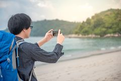 O mochileiro asiático novo toma fotos pelo smartphone Imagem de Stock